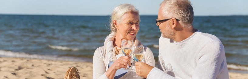 senior couple enjoying beverage on beach